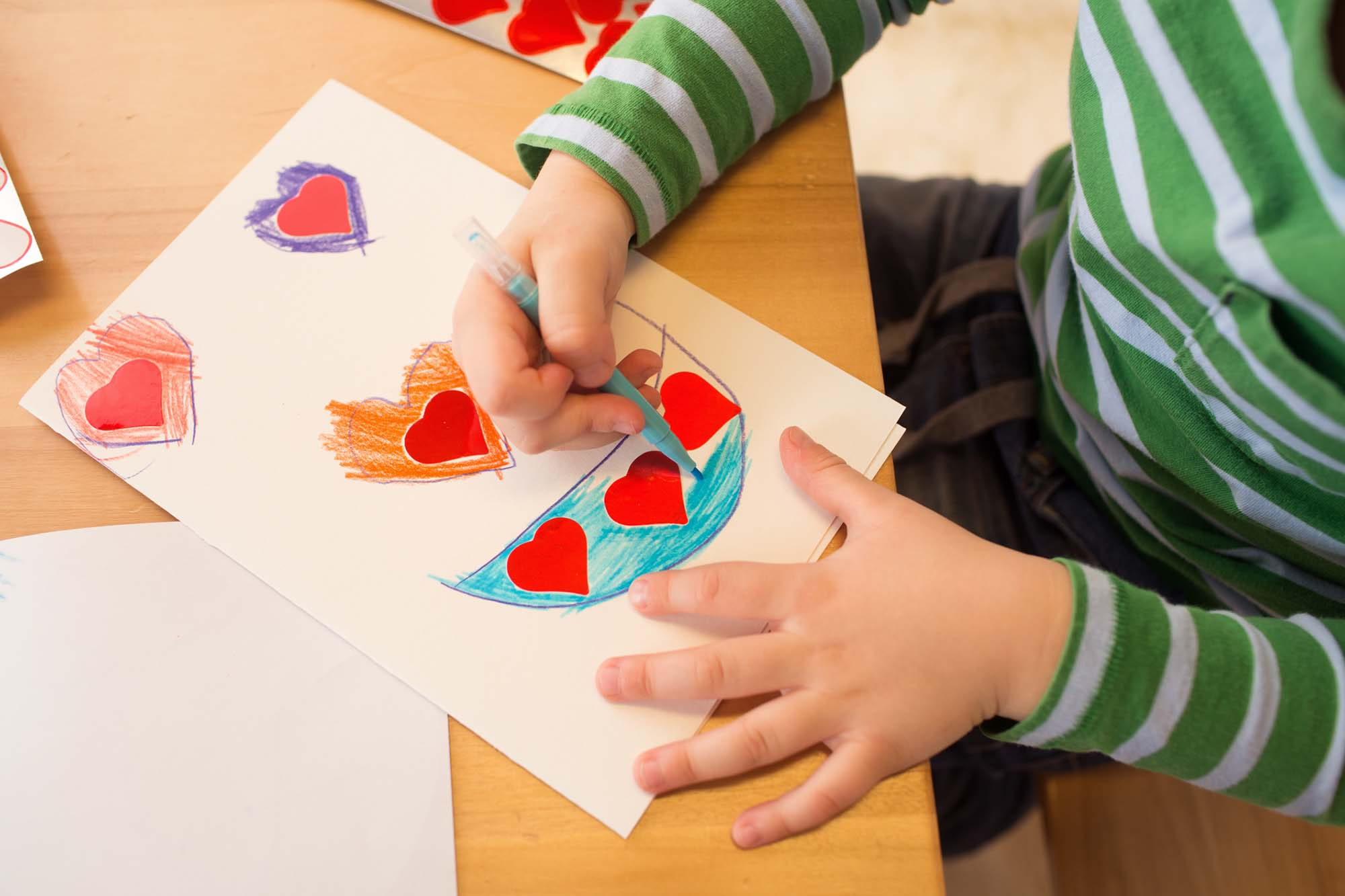 Kids, children, doing Valentine s day arts and crafts with hearts, pencils, paper