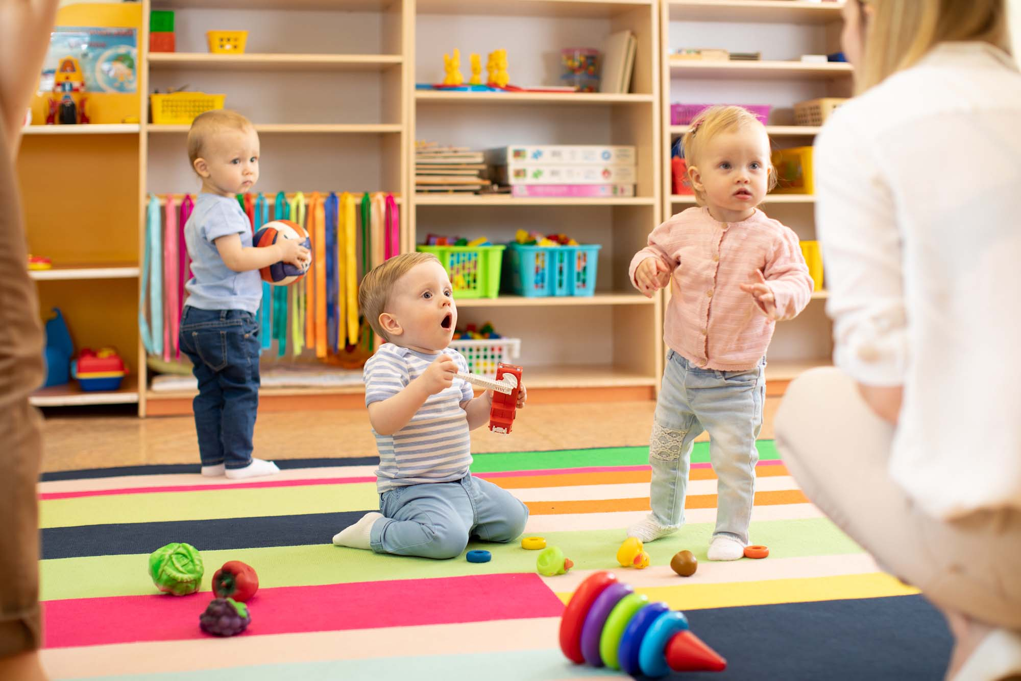Nursery babies play with carers or mothers on floor in day care centre
