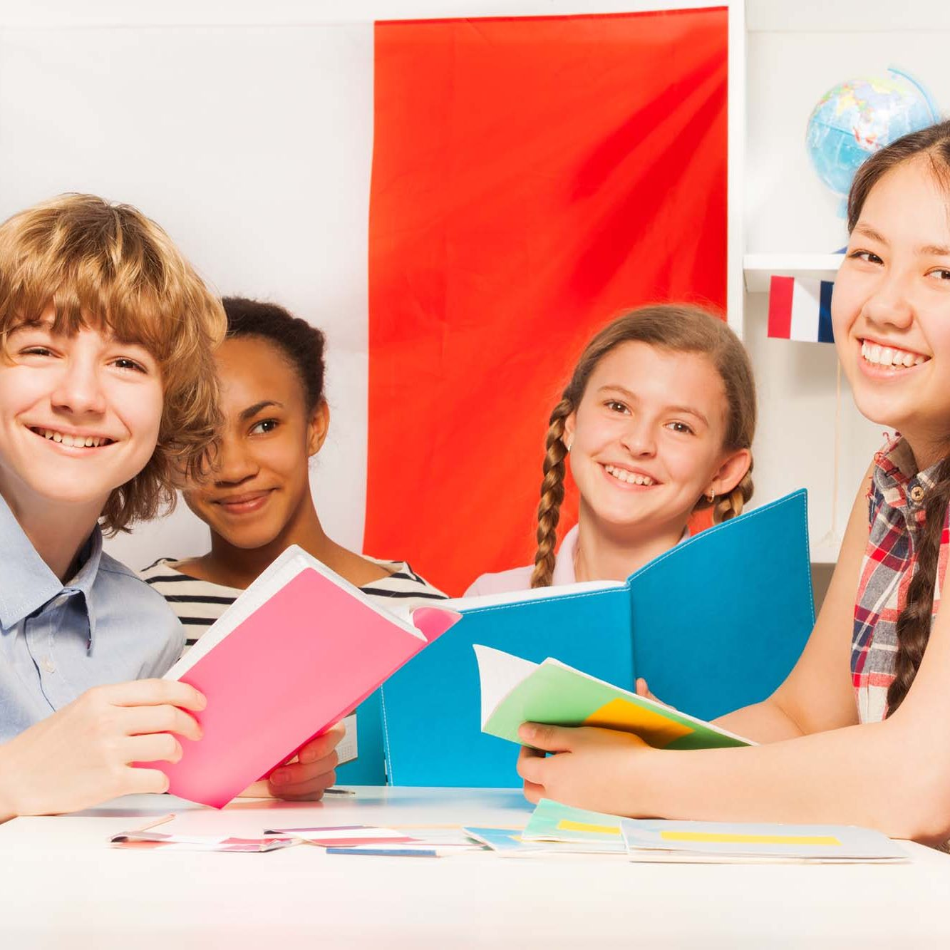 Four multiethnic teenage students learning French, reading books at the classroom