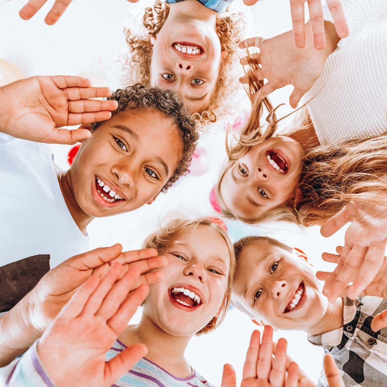 Group of happy children waving at the camera