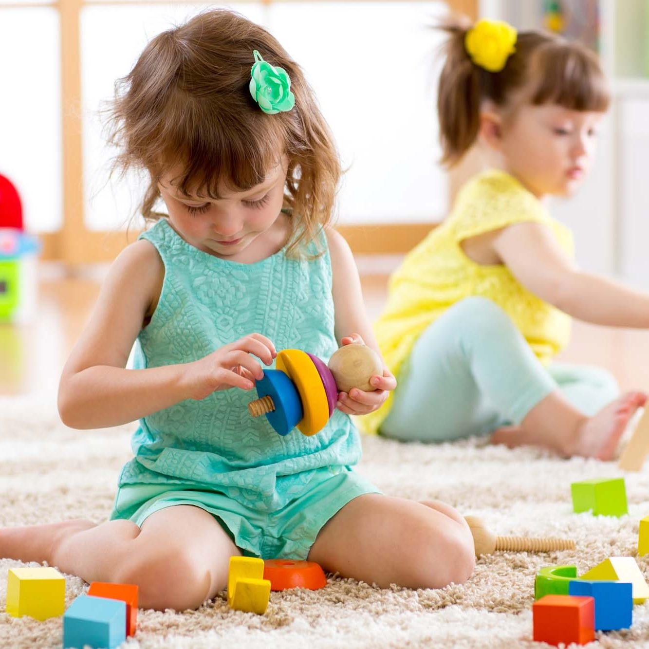 Children preschooler girls play logical toy learning shapes, arithmetic and colors at home or nursery