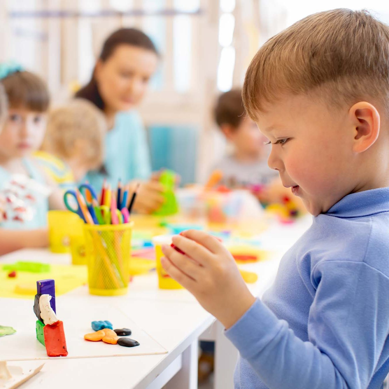 Child boy and group of kids working with colorful clay toy in nursery. Creative child molding in kindergarten. Preschoolers play with plasticine or dough.
