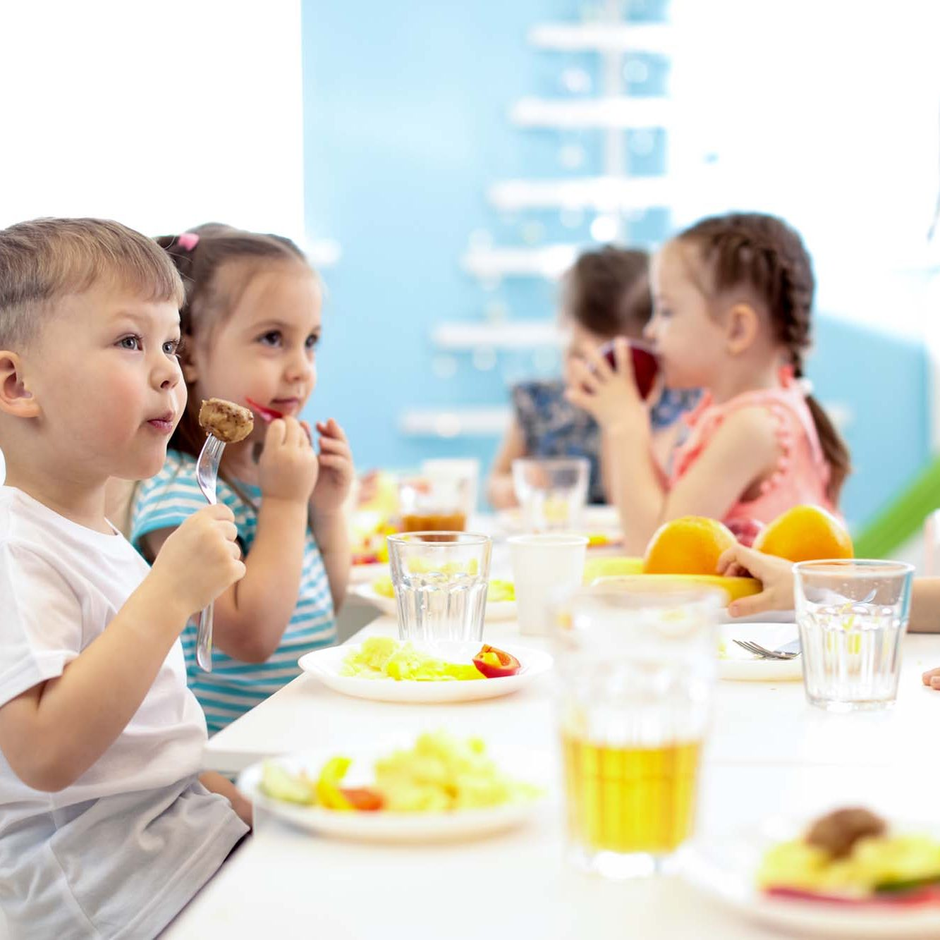 Group of kids have a lunch in day care centre. Children eating healthy food in kindergarten